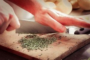 Mann am Gemüse schneiden